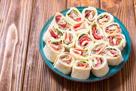 Sliced sandwich tortilla with tomatoes , salad , cream cheese and ham . Wrap rolls Stock Photo