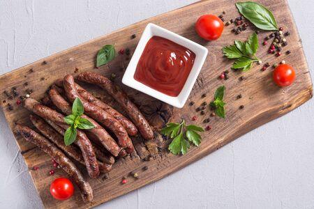 Saucisses grillées avec tomates, poivre et romarin. Fond de nourriture barbecue Banque d'images