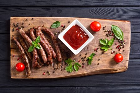 Grilled sausages with tomatoes , pepper and rosemary`. BBQ food background Banco de Imagens