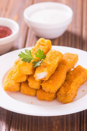 Fried fish sticks ( fingers ) or chicken nuggets . Snack food Banco de Imagens