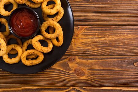 Crunchy fried onion rings and ketchup . Crispy snack food background