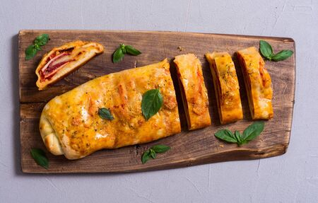 Italian food Pizza roll stromboli with cheese, salami, olives and tomatoes