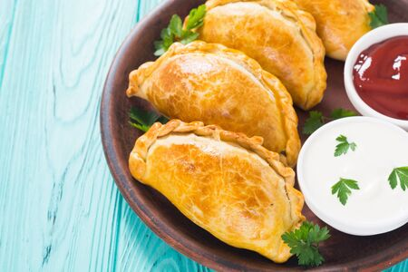 Latin American baked beef empanadas with sauces. Food background