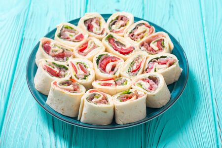 Sliced sandwich tortilla with tomatoes, salad, cream cheese and ham. Wrap rolls Stock Photo