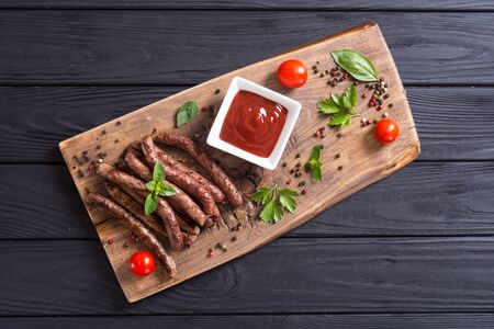 Grilled sausages with tomatoes, pepper and rosemary. BBQ food background