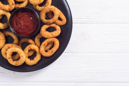 Crunchy fried onion rings and ketchup. Crispy snack food background