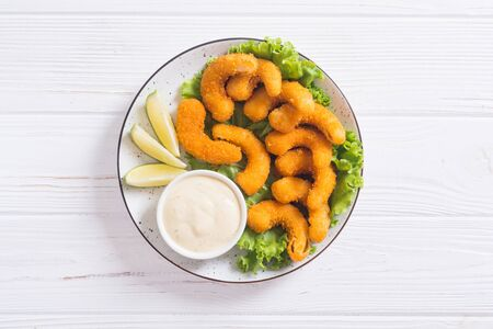 Shrimps in batter with sauce and lime. Fast food on rustic background Stock Photo