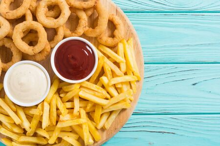 French fries and onion rings with sauces on wooden board Stock Photo