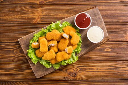 Chicken golden nuggets on wooden board. Unhealthy fast food