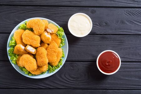 Chicken golden nuggets in plate on rustic background. Unhealthy fast food