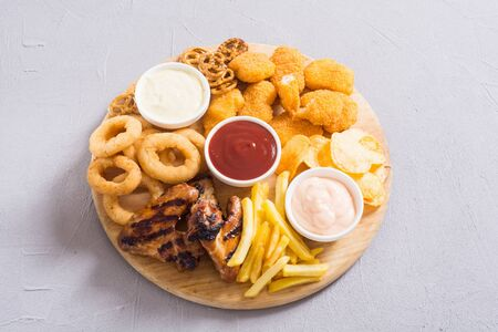 Onion rings, nuggets, grilled wings, french fries mix of snacks and sauces.