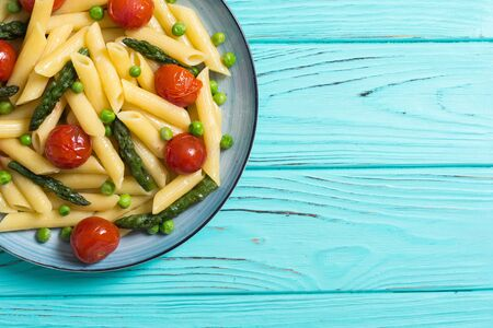 Penne pasta salad with asparagus , tomatoes and peas . Food background Stok Fotoğraf