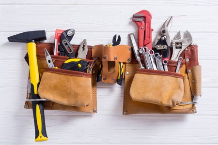 Tool belt with hand tools . Work background on wooden board Фото со стока