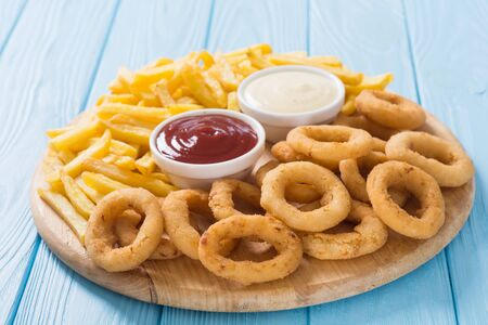 French fries and onion rings with sauces on wooden board