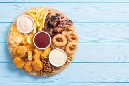 Onion rings , nuggets grilled wings , french fries mix of snacks and sauces . Beer board 免版税图像 - 130668913