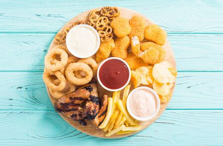 Onion rings , nuggets grilled wings , french fries mix of snacks and sauces . Beer board Stock fotó