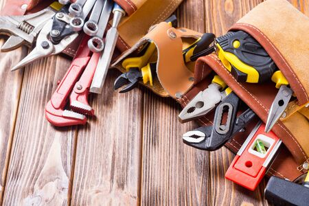 Tool belt with hand tools . Work background on wooden board Stock fotó