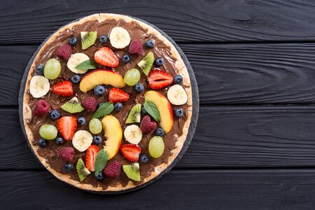 Fruit pizza with nut nougat cream , fruit and berries . Sweet dessert