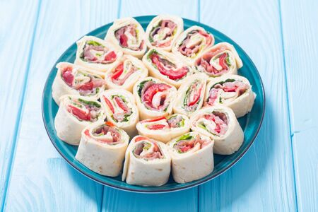Sliced sandwich tortilla with tomatoes , salad , cream cheese and ham . Wrap rolls Stock fotó