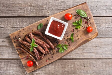 Grilled sausages with tomatoes , pepper and rosemary`. BBQ food background Stock fotó