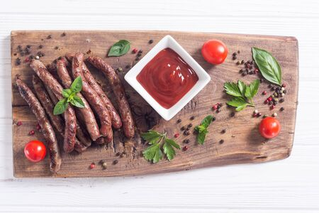 Grilled sausages with tomatoes , pepper and rosemary`. BBQ food background