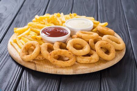 French fries and onion rings with sauces on wooden board Stock fotó