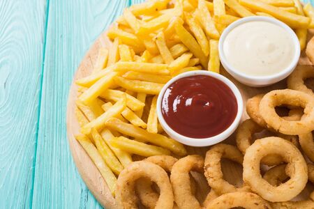 French fries and onion rings with sauces on wooden board Stock fotó - 144207078