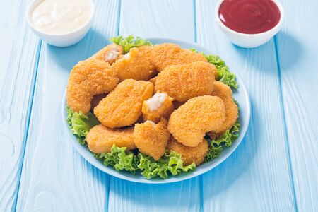 Chicken golden nuggets in plate on rustic background . Unhealthy fast food Stock fotó