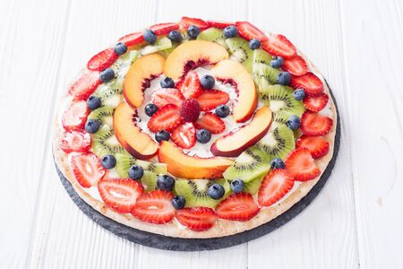 Fruit pizza with fruit and berries . Sweet tasty dessert