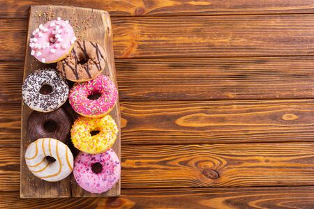assorted donuts with chocolate frosted, pink glazed and sprinkles . Top view