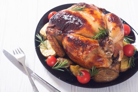 Baked chicken with pototoes , chery tomatoes and rosemary . Food background