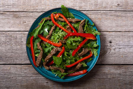 Healthy salad with beef red pepper and arugula. Food on wooden background