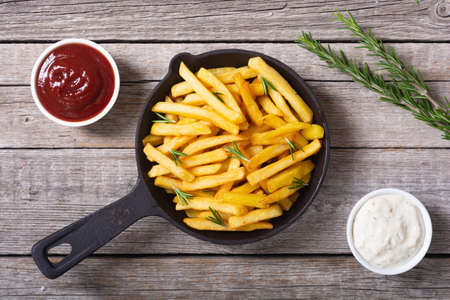 French fries with rosemary and ketchup. Fastfood background