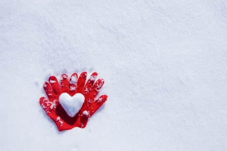 Heart and gloves on snow photo