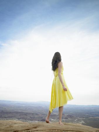 strata: Giovane donna in abito cercando in strati di roccia (vista posteriore)