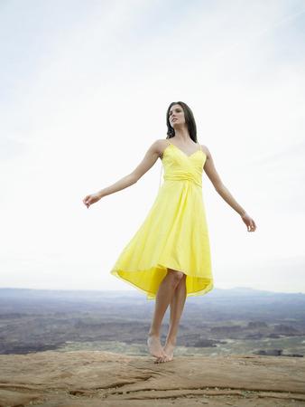 strata: Giovane donna in abito giallo, strati di roccia in background (inquadratura dal basso)