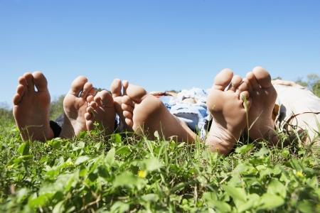 четыре человека: Barefeet из четырех человек на лужайке (крупным планом)