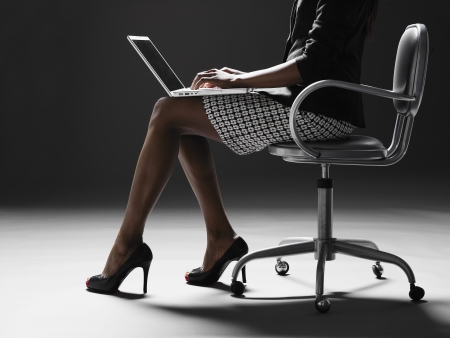Businesswoman using laptop (low section) photo