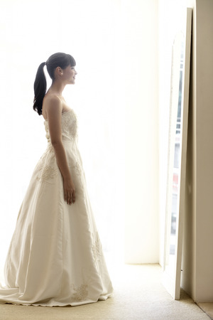 Young woman trying wedding dress on photo