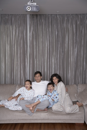 Parents with two children watching TV photo