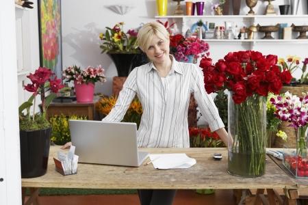 Female florist with laptop (portrait) Stock Photo
