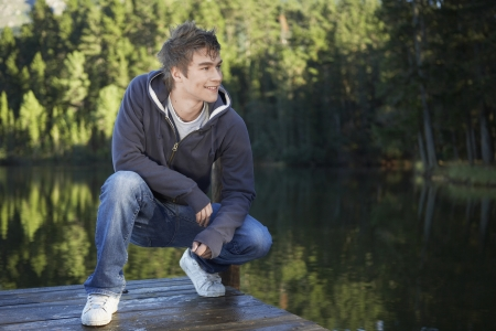 casual hooded top: Teenage boy crouching on jetty