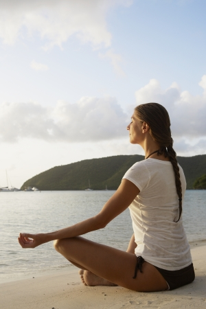 Mid adult woman meditating in lotus position on sandy beach, St. John, US Virgin Islands, USA photo