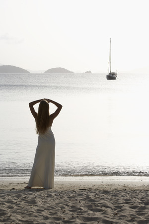 Mid adult woman looking at sailboat in sea, St. John, US Virgin Islands, USA photo
