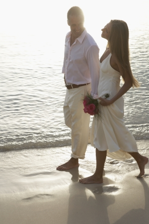 Newlyweds walking on sandy beach, St John, US Virgin Islands, USA photo