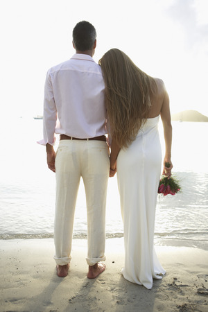 Newlyweds looking at view on beach (rear view) photo