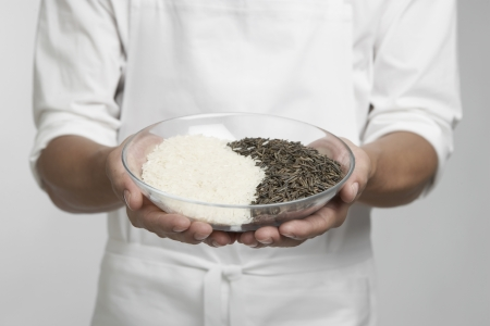 Chef holding bowl of white and wild rice (mid section) photo