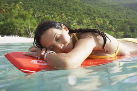 Young woman floating on bodyboard near beach photo