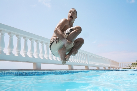 Mid adult man jumping into swimming pool Stock Photo