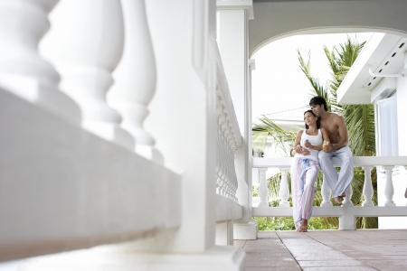 Young couple with mugs standing on terrace (low angle view) photo